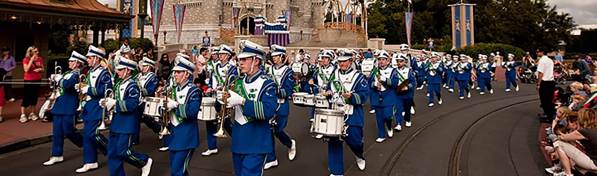 A marching band performing for park Guests