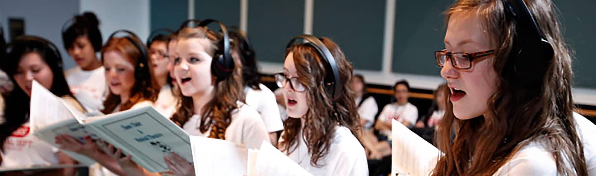Young performers wearing headphones and holding binders with sheet music