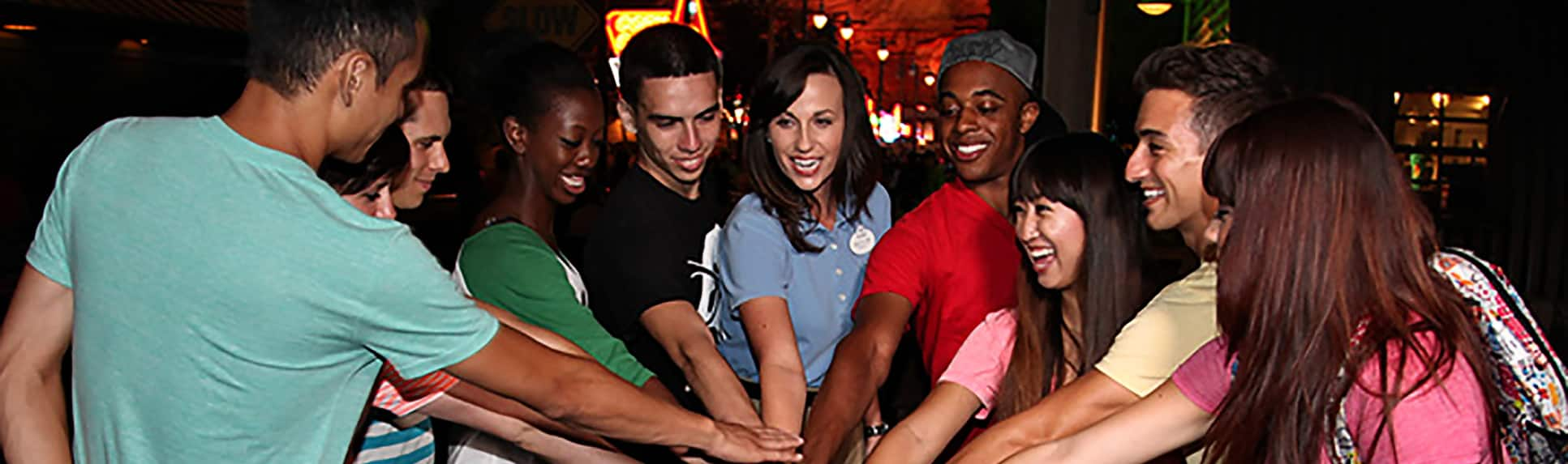 A Cast Member and young adults putting their hands together in a group huddle