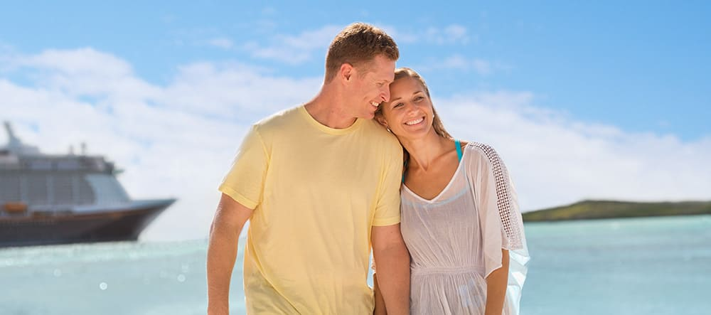 A man and woman lean in close together while standing near a cruise ship