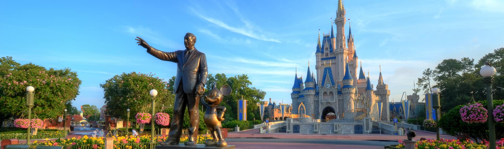 A statue of Mickey Mouse and Walt Disney holding hands in front of Cinderella Castle at Magic Kingdom park