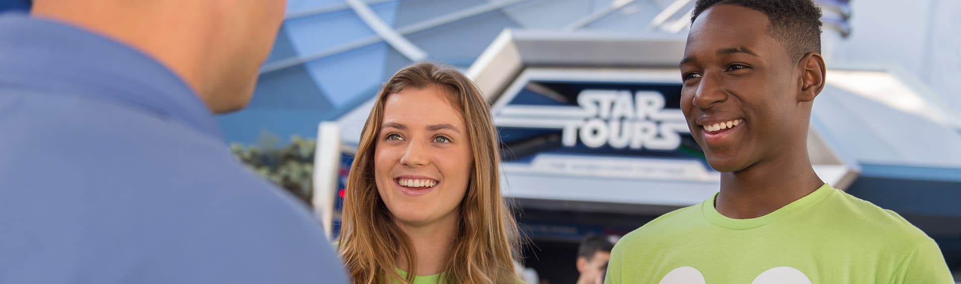 A young woman and 2 young men wearing Disney tee shirts smile as they chat with another man outside the Star Tours attraction