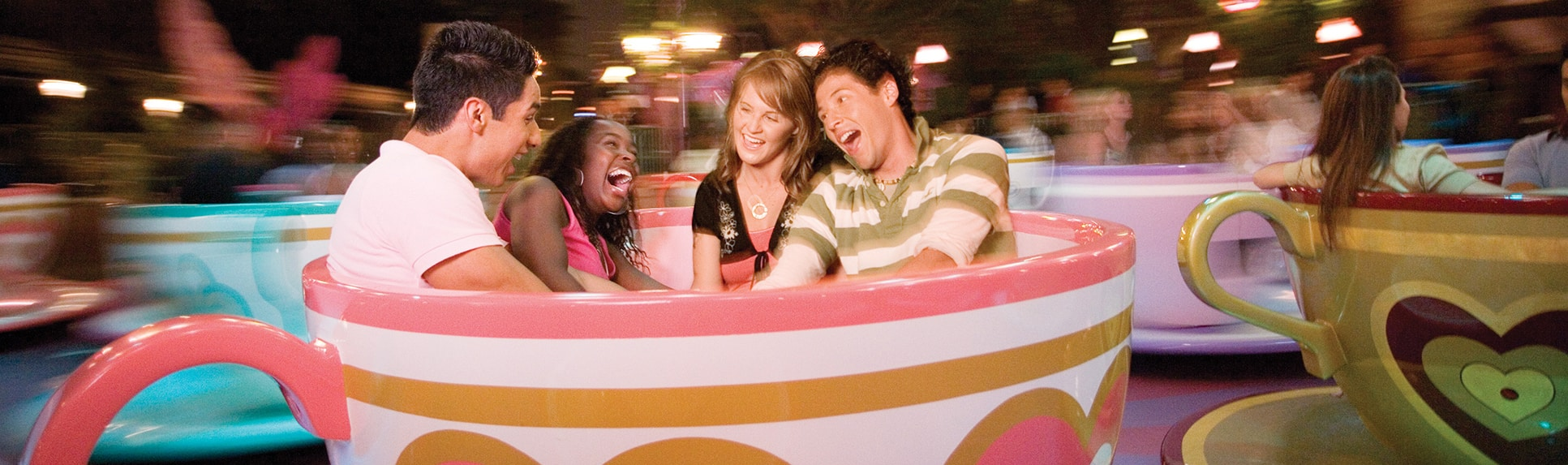 Smiling people spinning on the Mad Tea Party attraction teacups in the evening