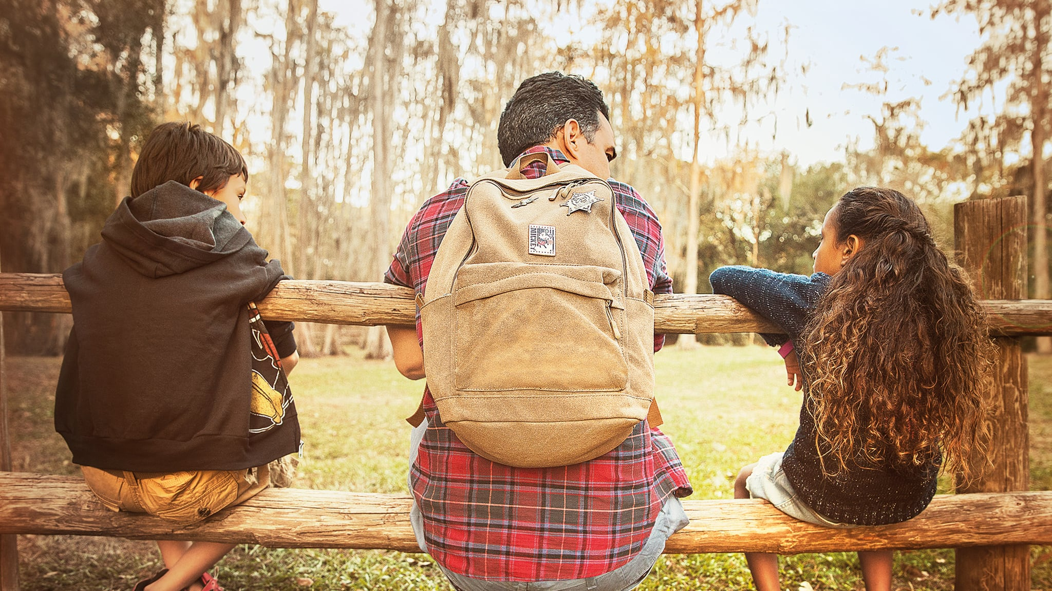 A father wearing a backpack sits in between rungs of a  wooden fence with his 2 children