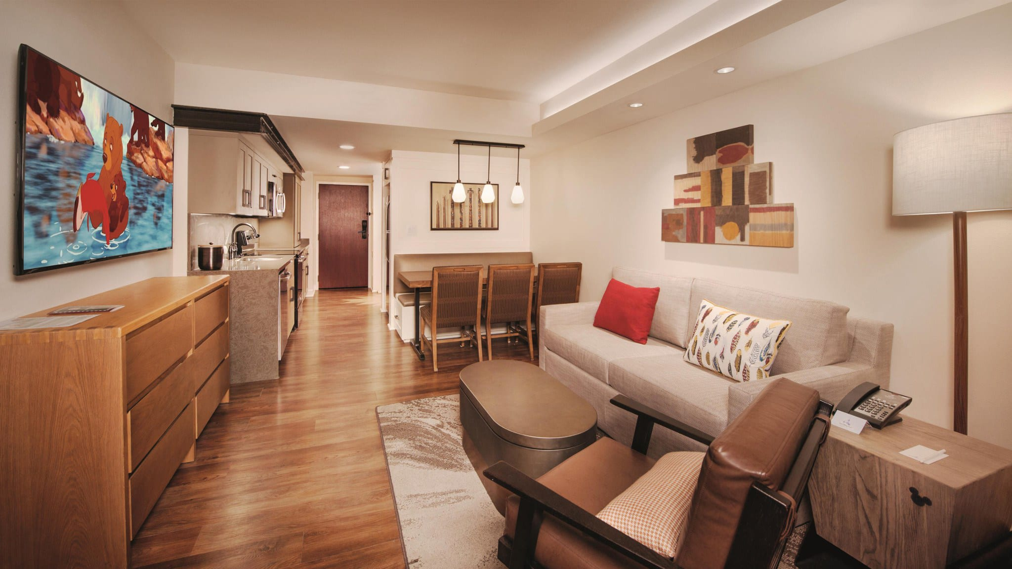 Living area with sleeper sofa, armchair, coffee table with storage, dining table and chairs, hanging accent lights, artwork, dresser, flat panel TV and kitchenette.