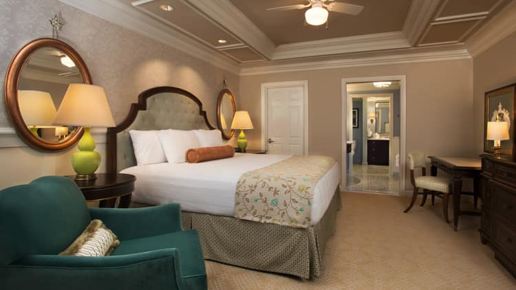 A bedroom with a bed  quilted headboard  armchair  mirrors and a dresser. The Villas at Disney s Grand Floridian Resort   Spa   Disney