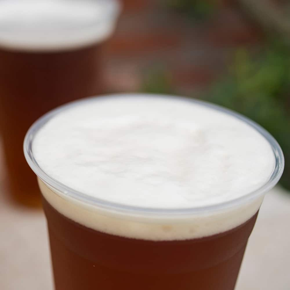 Foam-topped cups of beer