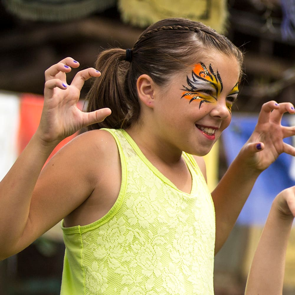 A young female Guest in ferociously themed face paint smiles while posing for a picture