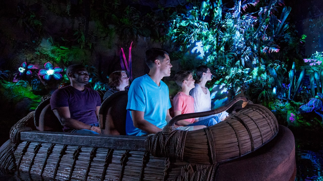A family looks on in wonder while riding a reed raft through the bioluminescent Na'vi River Journey